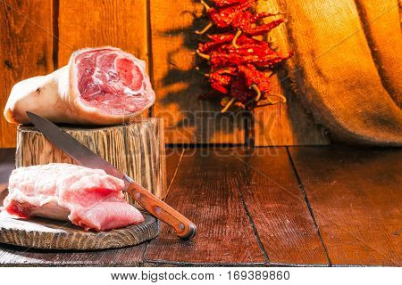 Pork shank on the buther block. Sliced loin on rustic board with knife. Chili pepper string on wooden wall