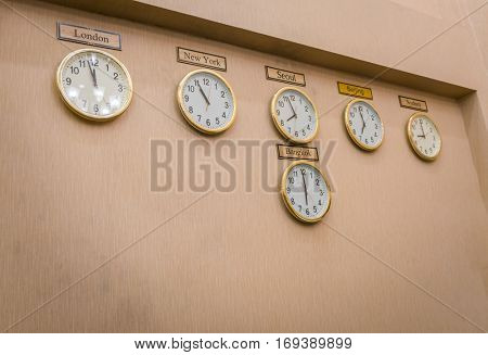 Clocks shows different time zones on old wall