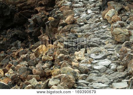 Grey and brown gravel stone or rock texture surface outdoors on sunny day on natural background