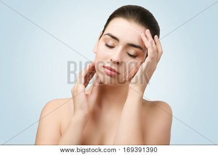 Plastic surgery concept. Young woman with marks on face against blue background