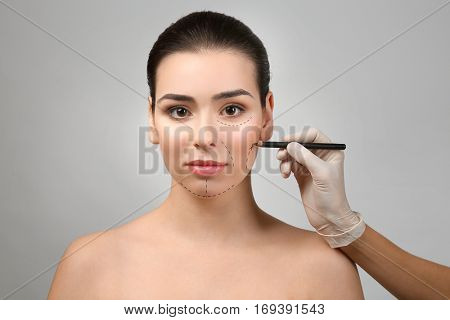 Surgeon drawing marks on female face against gray background. Plastic surgery concept