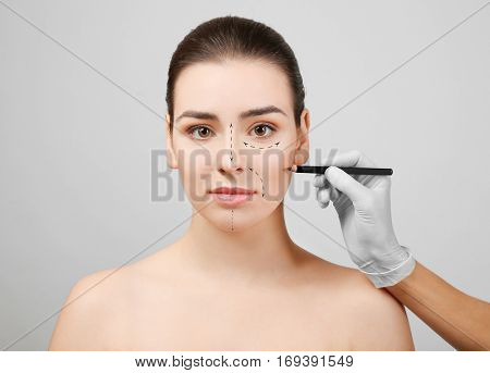 Plastic surgery concept. Doctor drawing marks on female face against gray background