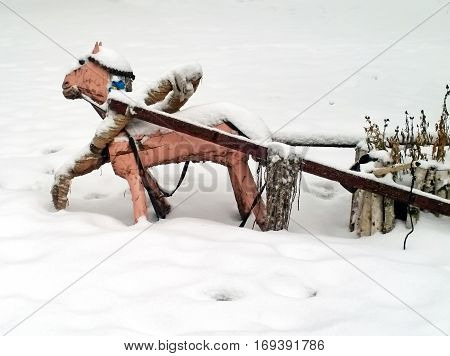 Wooden horse harnessed to a cart made with his own hands in the snow
