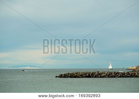 Beautiful sailing and motor boats float in calm blue sea water inshore along rocky coast outdoors on sunny summer day on sky background
