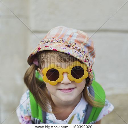 Cute smiling happy little girl with a backpack sitting on a bench. Child tourist in big old city. Kid in sunglasses during summer vacation. Happy little traveler with ponytails. Copy space.
