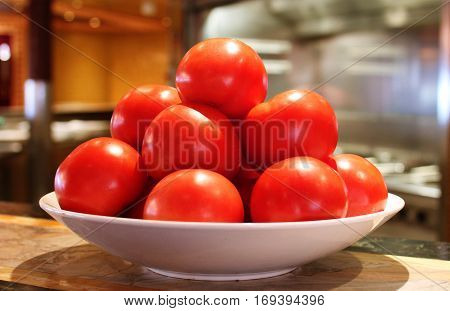 Luscious red tomatoes stacked on a white dish, interior, kitchen setting