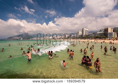 Rio de Janeiro, Brazil - January 15, 2017: Sunny summer day in Arpoador beach and the water is full of people enjoying waves.