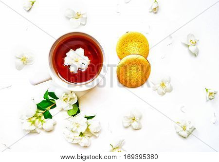 Tea Cup With Jasmine Flowers And Biscuits On White Background