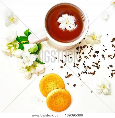 Tea Cup With Jasmine Flowers And Cookies In White Background