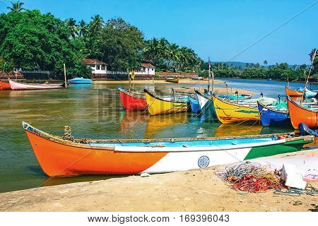Wooden fishing boats on the beach in tropical bay with palms huts and blue sky. Goa India