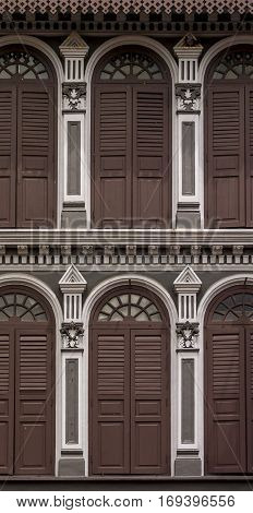 Detailed brown, ornate building facades, in China Town, Singapore, Asia, with archways and shutters for each window
