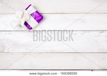 Violet gift box with bow on white wood background
