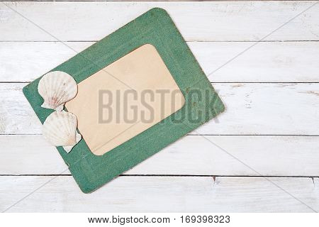 Old green photo frame with two sea shells on white wooden background