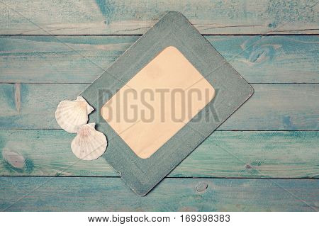 Old green photo frame with two sea shells on wooden background