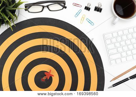 Dart target arrow hitting on bullseye in dartboard over office desk table background with eye glasses pen pencil computer and cuo of coffee