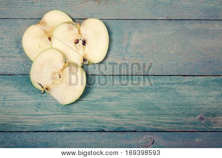 Three of ripe apple slices on old wooden background. top view