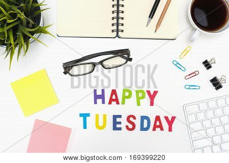 Office desk table with supply pen pencil notebook computer eye glasses sticky note cup of coffee and happy tuesday word on white background