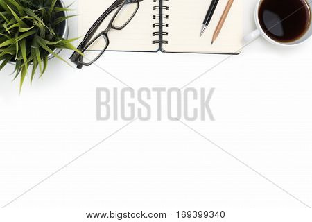 Open spiral blank notebook with eye glasses pen pencil cup of coffee and small flower plant on white desk table background with copy space flat lay top view