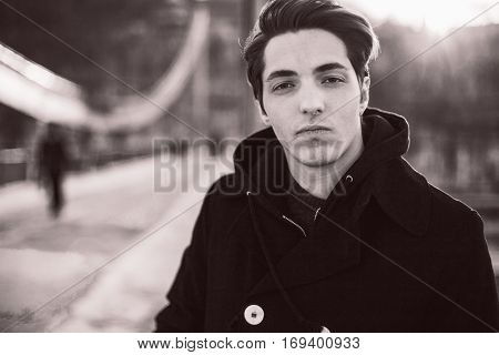 Retro portrait of a confident hipster guy standing on the bridge looking at camera. Film sepia effect with grain