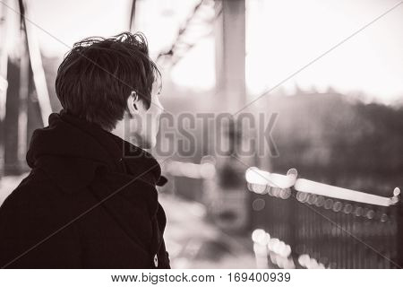 Hipster guy standing on the bridge looking away. Black and white retro photo with grain