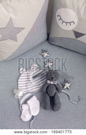 round white baby bed with gray pillows and plush rabbit