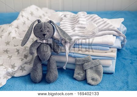 baby clothes with diapers are stacked with a pacifier and a toy rabbit