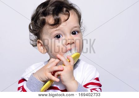 Portrait of a cute curly hair baby trying to comb his hair. Adorable one year old child being funny eating his hair brush.