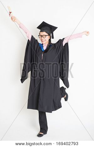 University student in graduation gown and cap hand raised holding diploma certificate jumping around. Full body portrait of east  Asian female model standing on plain background.