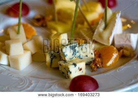 Delicious cheese plate with blue roquefort brie camambert gauda with garnishes grapes oranges and nuts on white porcelain background