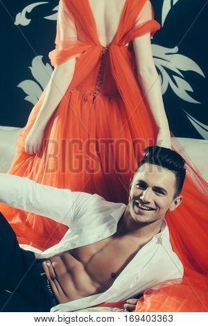 young couple of handsome man in open shirt with muscular bare torso with pretty sexy woman in red elegant evening dress with long skirt