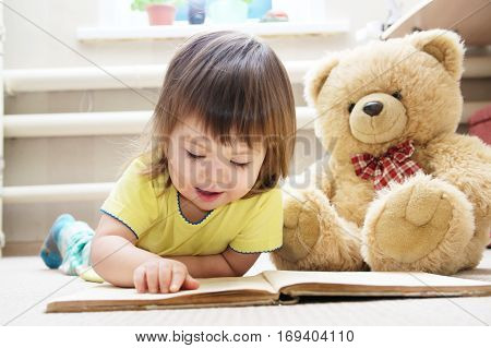 little girl reading book lying on stomach in her room on carpet with toy Teddy bear smiling cute child children education and development happy childhood
