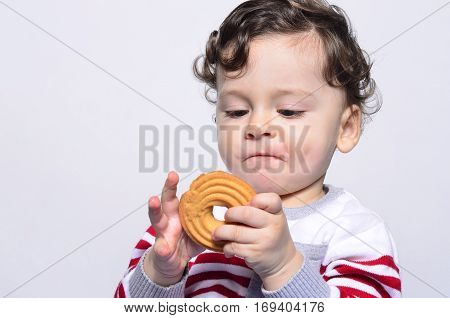 Portrait of a cute baby eating a biscuit looking at it curiously. One year old kid eating biscuits by himself. Adorable curly hair boy being hungry.