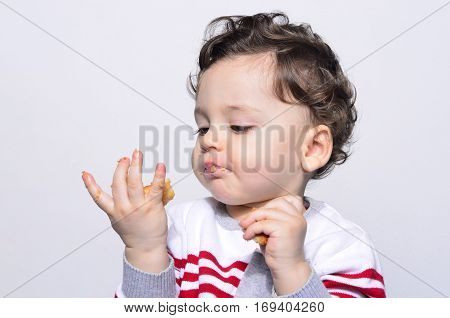 Portrait of a cute baby eating a biscuit looking at the hand.One year old kid eating biscuits by himself. Adorable curly hair boy being hungry.