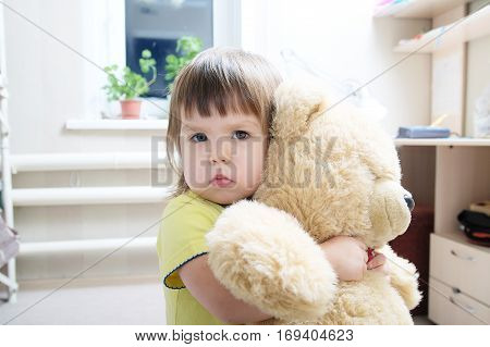 Baby Girl Hugging Teddy Bear Indoor In Her Room, Devotion Concep
