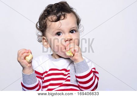 Portrait of a cute baby eating a banana.One year old kid eating fruits by himself. Adorable curly hair boy being hungry.