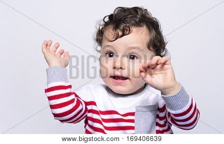 Cute baby boy crying raising his hands up.Little child in pain, suffering, teething, refusing and crying. Cute sad baby throwing a tantrum. Baby wants up in the arms to be held.