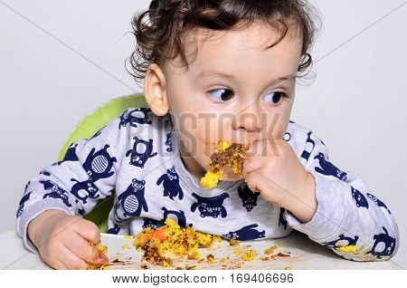 One year old kid eating a slice of birthday smash cake by himself getting dirty.Portrait of a cute baby eating cake making a mess. Adorable curly hair boy being hungry.
