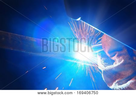 welder in a protective mask in a dark shop floor weld metal parts. By welding sparks fly