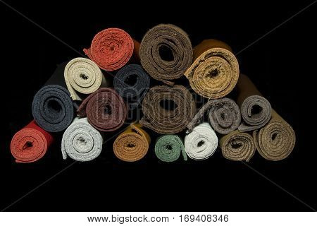 Rolls of different colored and textured leather, piled together. Isolated on a black background.