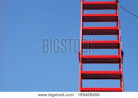 Signal red fire ladder from metal against the clear blue sky generous copy space