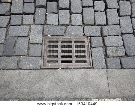Water Drainage Hole With Grid On A Cobbled Street
