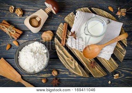 Ingredients for cooking baking in rural kitchen. Flour milk nuts and spices on vintage wood table from above