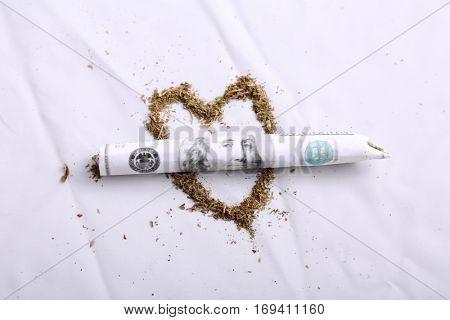 Marijuana Joint rolled up in American money. Marijuana is now legal recreationally in California. Legal Marijuana aka Joint, Pot, Spliff, Dope, Loco Weed, etc.