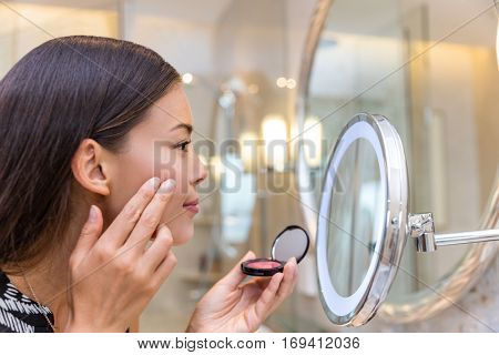 Asian young woman putting blush cream using fingers while looking in makeup mirror at home in bathroom. Morning routine of girl applying make-up before going to work. Face skincare.