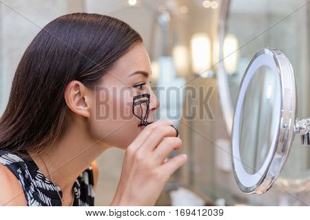 Woman using eyelash curler curling eyelashes before mascara in lighted round makeup mirror from luxury hotel or home bathroom. Beautiful Asian girl getting ready in the morning looking at reflection.