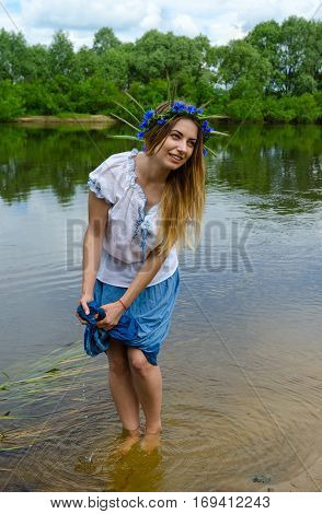 Beautiful young woman in wreath from cornflowers on river bank squeezes out wet hem of her skirt