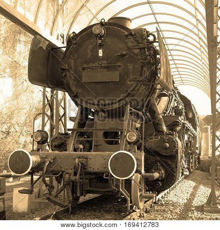 Old steam locomotive closeup. Sepia toned