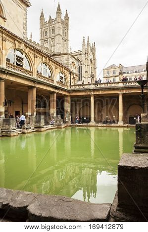 Bath Somerset United Kingdom - June 19 2006: Tourists at the ancient Roman Baths Museum. Bath Abbey and Roman Baths with green water reflection under cloudy sky.