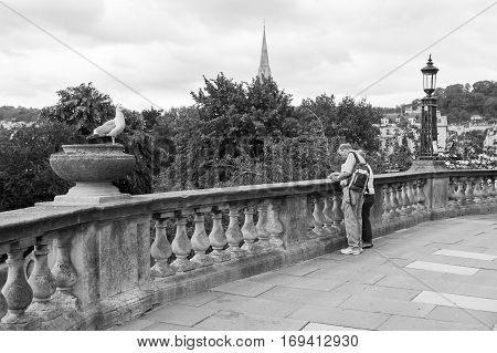 Bath Somerset United Kingdom - June 19 2006: Senior couple using map and looking for the direction on the terrace in city of Bath. Traveling couple concept. Tourists enjoying their vacation in England. St Michaelaas church can be seen in the background.