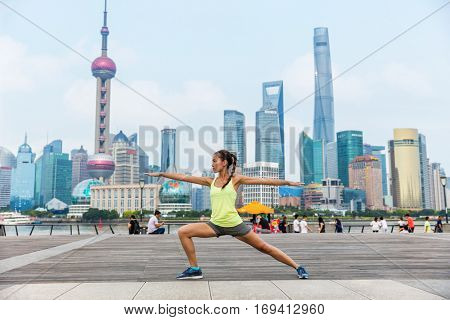 Yoga woman in warrior pose II doing urban workout fitness class on the Bund boardwalk, Shanghai city. Female yoga instructor working out training in chinese skyline background.